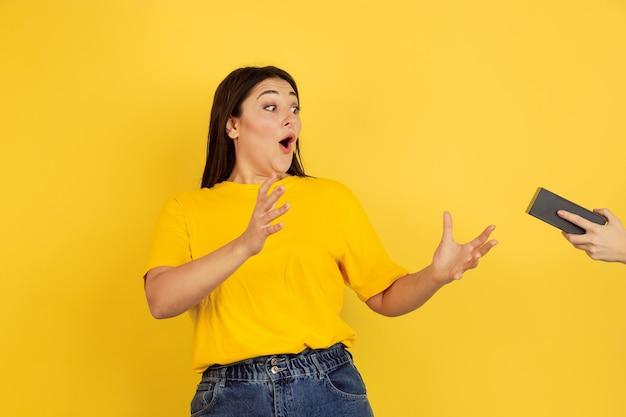 Prendere un regalo. ritratto della donna caucasica isolato sulla parete gialla. bellissima modella bruna femminile in stile casual. concetto di emozioni umane, espressione facciale, vendite, copyspace.