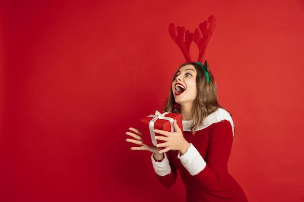 Prendendo regalo. biglietto d'auguri. concetto di natale, capodanno 2021, umore invernale, vacanze. bella donna caucasica con i capelli lunghi come la confezione regalo di cattura delle renne di babbo natale.