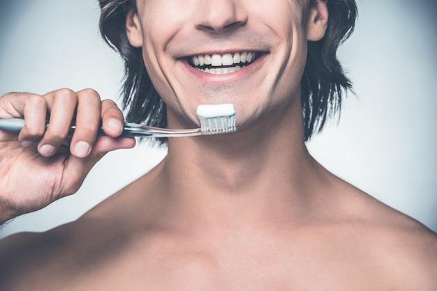 Prendersi cura dei miei denti. primo piano di un bel giovane uomo senza camicia che si lava i denti e sorride mentre sta in piedi su uno sfondo grigio
