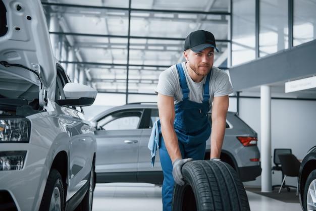 Togliendolo. meccanico in possesso di un pneumatico presso il garage di riparazione. sostituzione di pneumatici invernali ed estivi