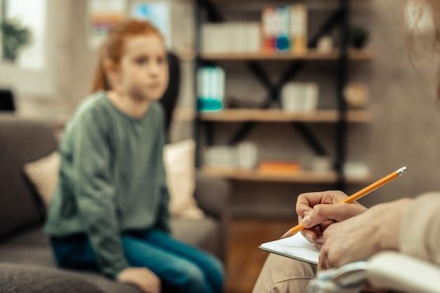 Prendere appunti. messa a fuoco selettiva di una matita utilizzata da un simpatico psicologo professionista per prendere appunti