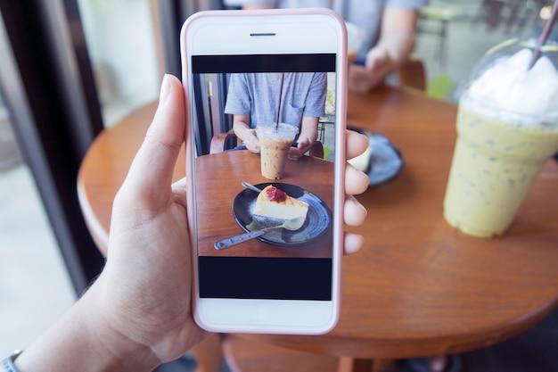 Scattare foto di un pezzo di torta e una tazza di caffè