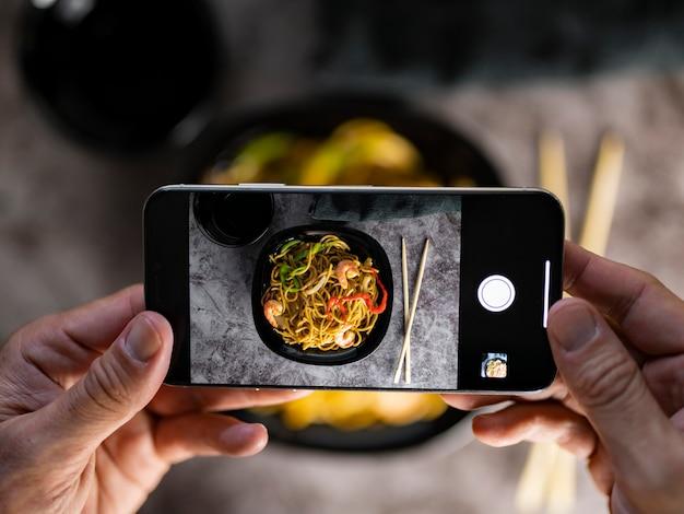 Scattare una foto con smarpthone di cibo asiatico