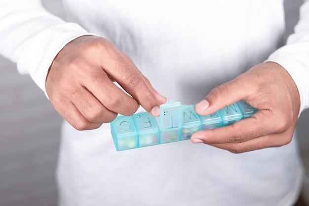 Prendendo pillole o capsule da una scatola di pillole.