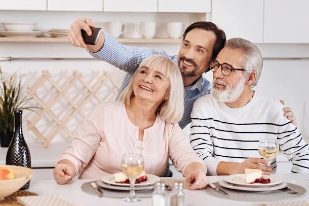 Scattare selfie per un album di famiglia. felice e divertito uomo sorridente cenando e godersi il tempo con i suoi genitori anziani tenendo il gadget e facendo selfie