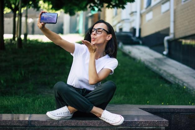 Fare un selfie! una foto a figura intera di una giovane studentessa, con gli occhiali, seduta fuori, con le gambe incrociate, che si fa un selfie, che mostra il canto della pace.