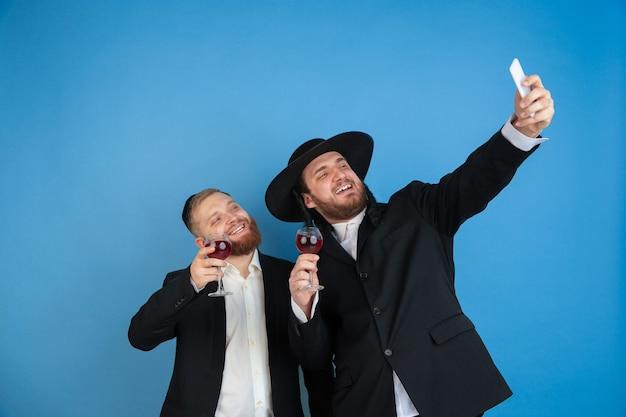 Prendendo selfie con il vino. ritratto di giovani uomini ebrei ortodossi isolati sulla parete blu. purim, affari, festival, vacanza, celebrazione pesach o pasqua ebraica, ebraismo, concetto di religione.
