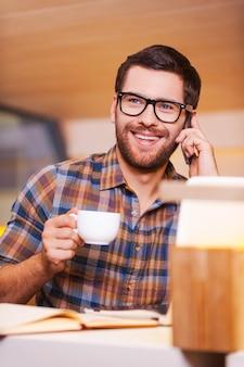 Prendersi del tempo per la pausa caffè. giovane allegro che parla al telefono cellulare e beve caffè mentre è seduto al bar