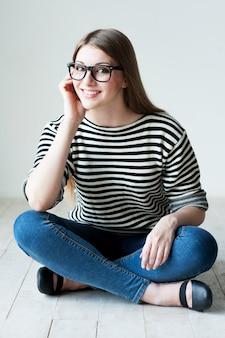 Prendersi del tempo per rilassarsi. bella giovane donna in abiti a righe seduta sul pavimento e sorridente