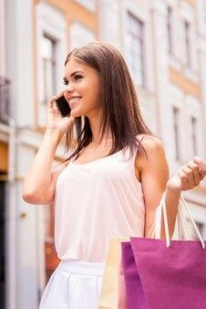 Prendendo con un amico sulle vendite. bella giovane donna sorridente che tiene le borse della spesa e parla al telefono cellulare mentre sta in piedi all'aperto