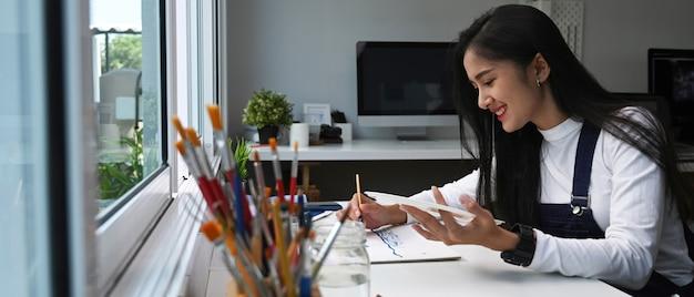 Artista femminile di talento dipinge su carta con acquerelli nel suo laboratorio