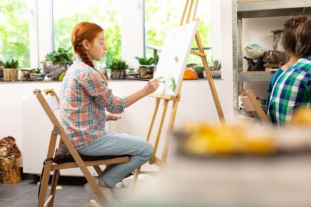 Ragazza di talento che si siede vicino al cavalletto da disegno e da colorare