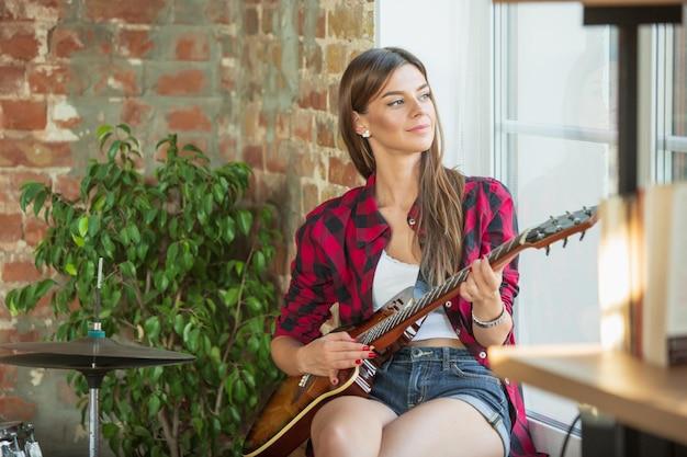 Talentuoso. studio musicale domestico, bella donna che registra musica, canta e suona la chitarra mentre è seduta in un loft sul posto di lavoro oa casa. concetto di hobby, musica, arte e creazione. creazione del primo singolo.