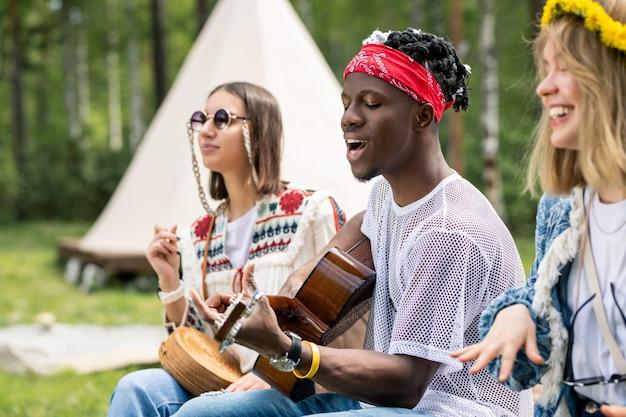 Talentuoso giovane ragazzo nero suonare la chitarra e cantare cantare mentre si gode una festa in campeggio con gli amici intimi