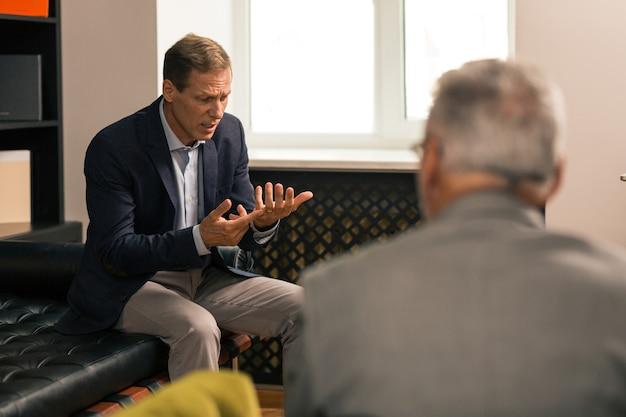 Parlare con un dottore. sconvolto uomo sposato dai capelli castani che discute dei suoi problemi personali con il suo medico mentre è seduto sul divano