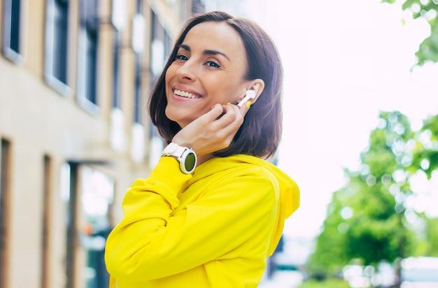 Parlare con un amico. un primo piano di una splendida ragazza in una felpa gialla con unghie gialle, parlando al telefono a mani libere con cuffie bluetooth.