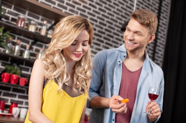 Parlare con l'uomo. bella ragazza bionda alla moda che parla con il suo bell'uomo che beve del vino rosso