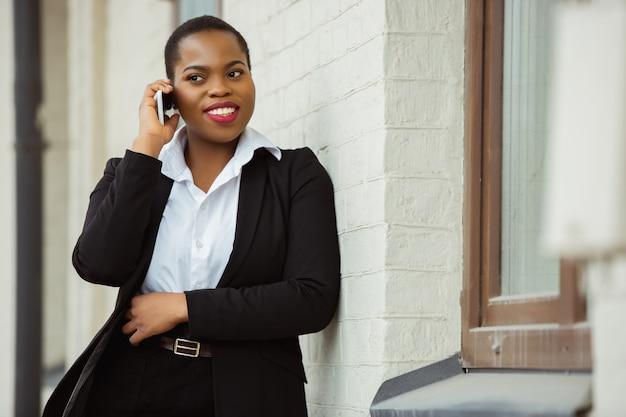 Parlando al telefono la donna d'affari afroamericana in abbigliamento da ufficio sorridente sembra sicura