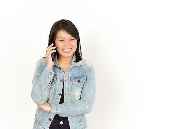 Parlando al telefono di una bella donna asiatica che indossa giacca di jeans e camicia nera isolata su bianco