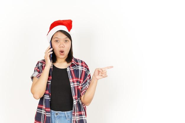 Parlando al telefono e indicando da parte una donna asiatica che indossa una camicia a quadri rossa e un cappello da babbo natale