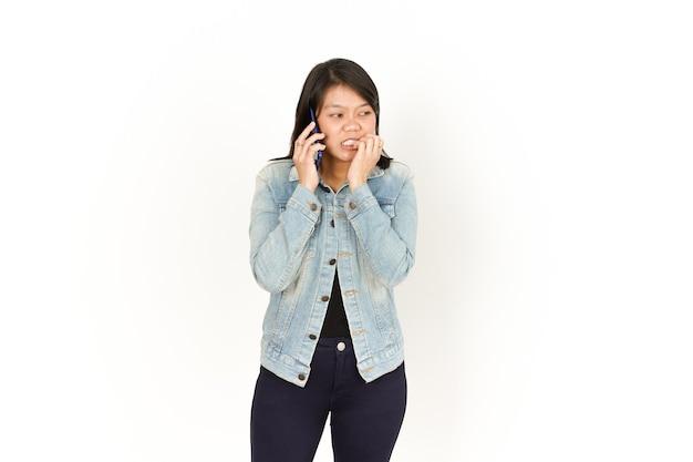 Parlando al telefono con la faccia impaurita di una bella donna asiatica che indossa una giacca di jeans e una camicia nera