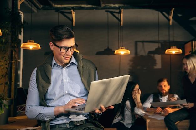 Colloqui. colleghi che lavorano insieme in un ufficio moderno utilizzando dispositivi e gadget durante riunioni creative.
