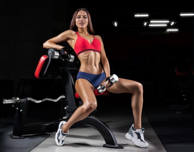 Donna atletica alta in posa in palestra su una panchina con un manubrio.