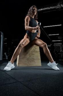 Donna atletica alta in posa in palestra su una panchina con manubri. bicipiti pompaggio.