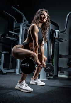 La donna atletica alta sorride e si accovaccia con un bilanciere in palestra. deadlift.