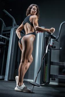 Alta donna atletica sorridente e in posa in palestra con un bilanciere in metallo. vista posteriore.
