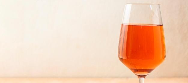 Un bicchiere alto e trasparente di ricco vino arancione.