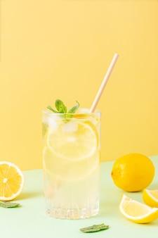 Bicchiere alto di tè freddo con limoni intorno e foglie di menta su sfondo giallo e menta