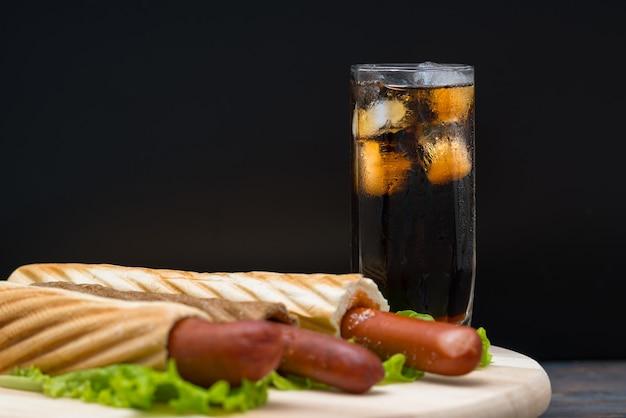 Bicchiere alto di soda con ghiaccio accanto al piatto di hot dog avvolti nel pane sopra grandi foglie di lattuga