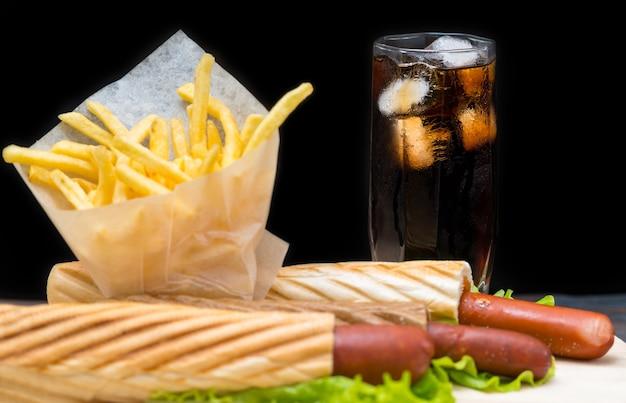 Bicchiere di soda alto con ghiaccio accanto a patatine fritte nella pellicola trasparente e hot dog avvolti in pane e foglie di lattuga sul piatto