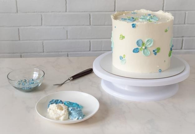 Torta bianca alta su un supporto con fiori blu decori crema e set per decorare e spatola sul tavolo.