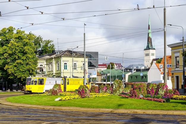 Tram giallo della città di tallinn che passa attraverso una piazza con molti fiori.