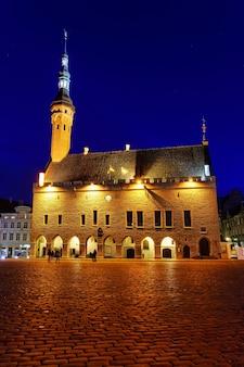 Piazza del municipio di tallinn illuminata di notte dopo la pioggia.