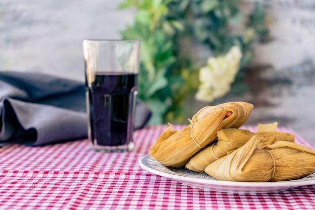 Tamales serviti su un tavolo tradizionale con un bicchiere di vino rosso. un tipico panino o pasto latino americano a base di farina di mais e carne. cibo tradizionale andino. concetto di cibo tradizionale