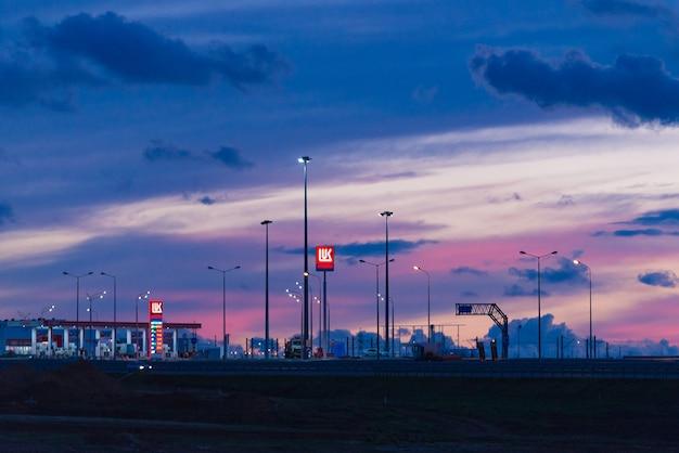 Taman, russia - ottobre 2018: stazione di servizio lukoil sul ponte di crimea al tramonto, notte. lukoil è una compagnia petrolifera russa.