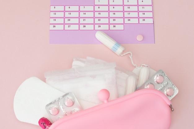 Tamponi, femminili, assorbenti per i giorni critici, calendario femminile, pillole per il dolore durante le mestruazioni su un rosa