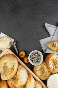 Focaccia tandoor, samsa, pasta cruda, farina e semi di sesamo. prodotti da forno uzbeki su una tavola nera.