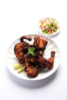 Pollo tandoori - preparato arrostendo il pollo marinato in yogurt e spezie in un tandoor. pezzi di gambe serviti in un piatto con insalata e chutney