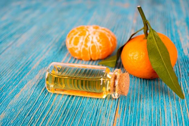 Olio essenziale di mandarino con frutti sul tavolo di legno turchese