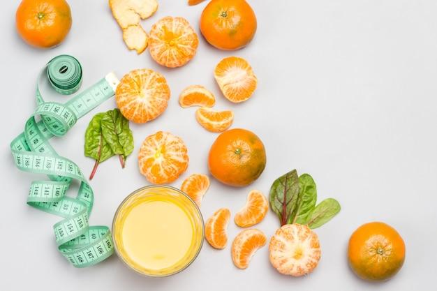 Frutti di mandarino, succo di agrumi in vetro e metro a nastro. lay piatto. copia spazio