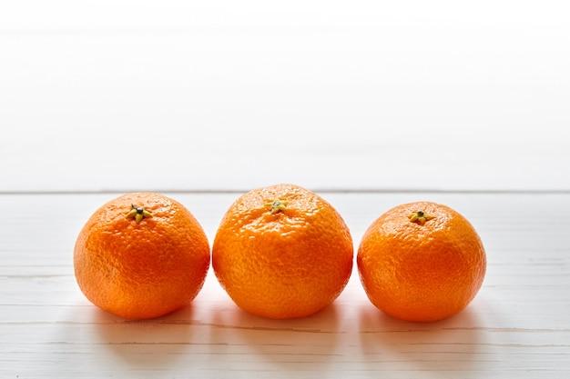 Frutti di mandarino su un tavolo di legno bianco