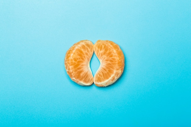 Fette di mandarino su uno sfondo minimale colorato in bianco. metafora della vulva femminile. creatività e concetto di idea.
