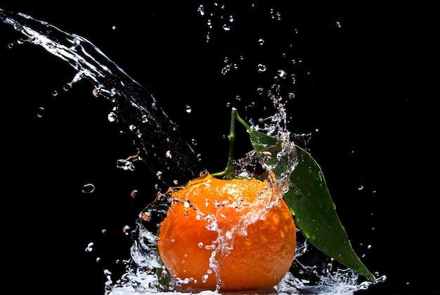 Mandarino con foglie verdi e spruzzi d'acqua isolati sul nero