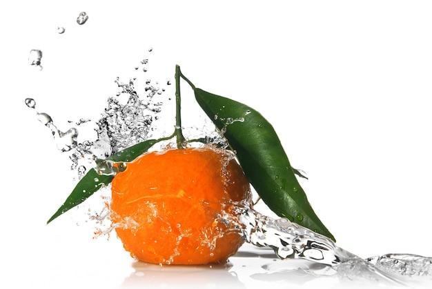 Mandarino con spruzzi d'acqua isolato su bianco