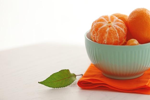 Mandarini in ciotola sulla tavola di legno bianca, fine su