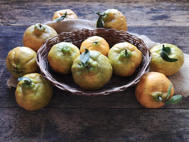 Mandarini frutta nel cestino su fondo di legno rustico.